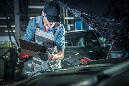 mecânico segurando uma prancheta anotando algo enquanto olha para o motor do carro